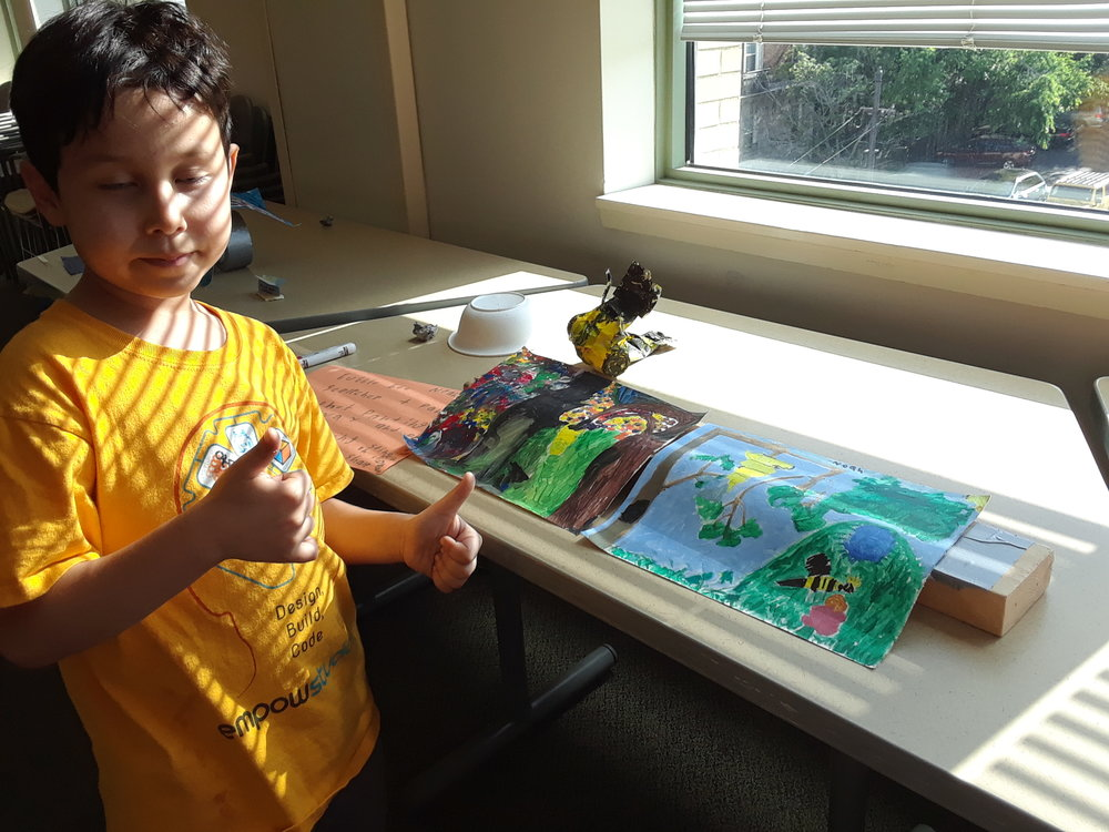 Student with his two paintings and sculpture inspired by bees.