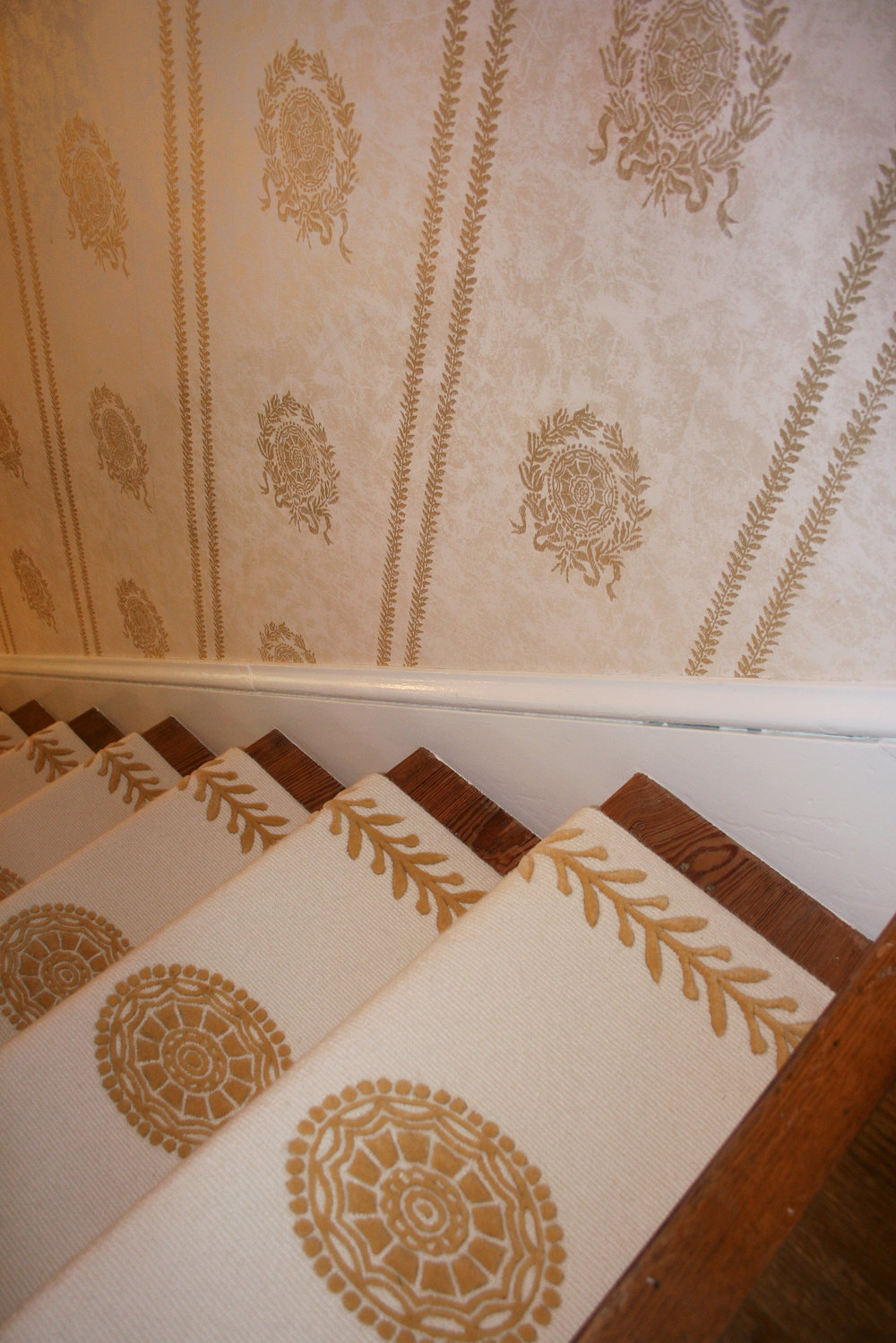 Beautiful custom design and custom installation stair runner in ivory and gold with a medallion to match the intricate wallpaper