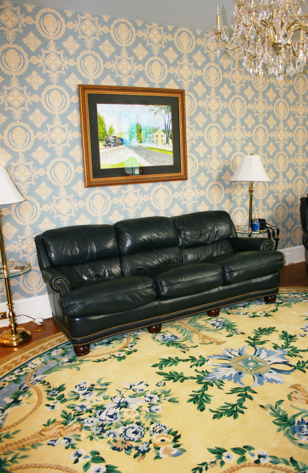 Custom design wool oval rug to coordinate with the elegant wallpaper