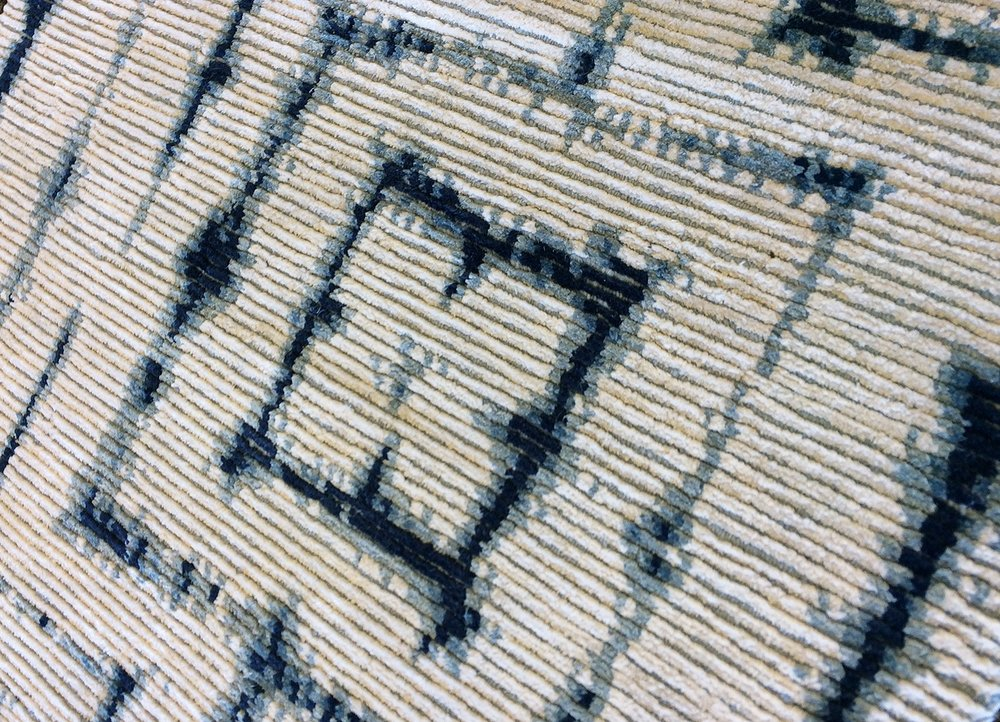 Hand-knotted rug sample with a blue, white, and gray geometric design