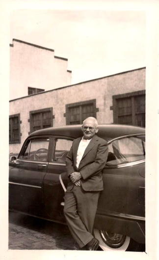 Harold Vaughn Lang and his car in front of the Lang Company building.