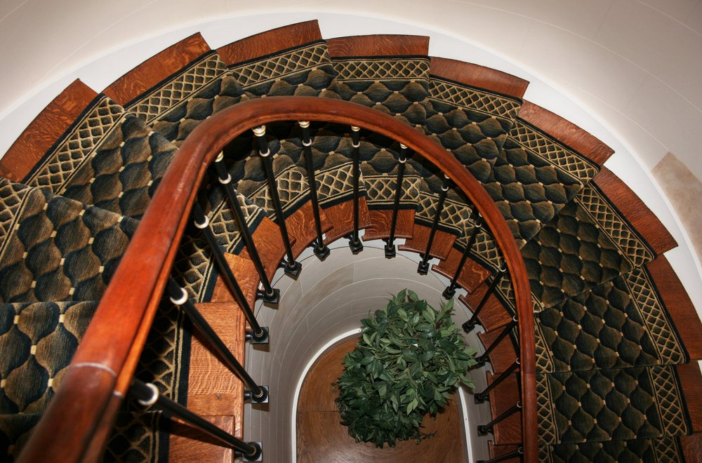 Black and gold custom carpet stair runner installed on a beautiful spiral staircase