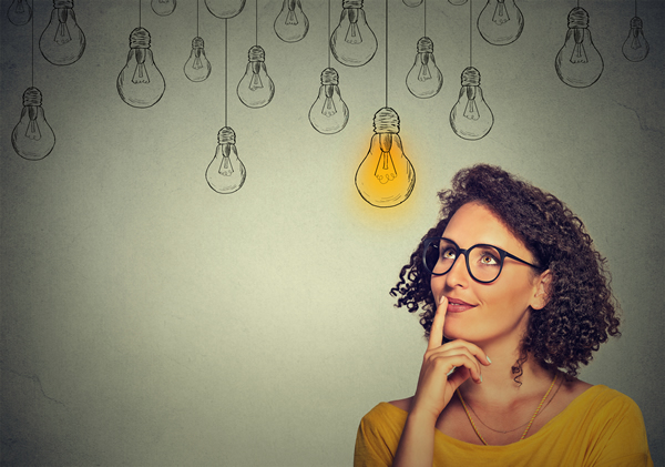 Woman in glasses thinking with lightbulb glowing above her head