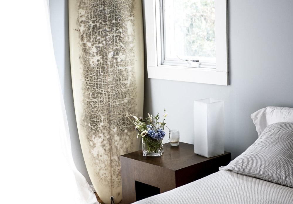 Amagansett Beach House peaceful bedroom interior blue side table surfboard