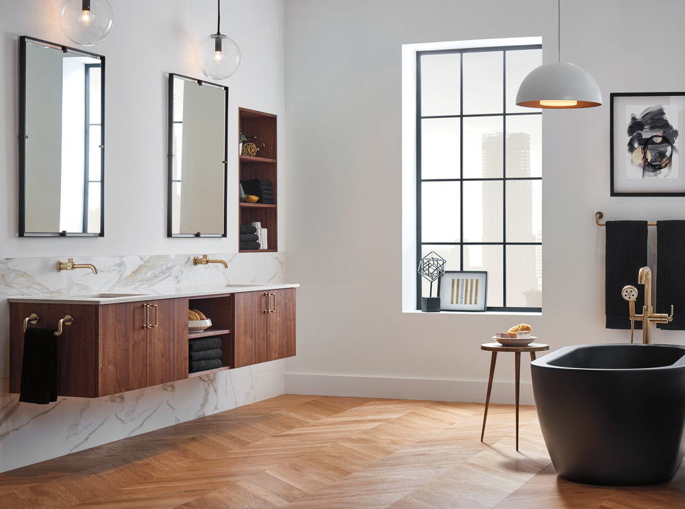 Brizo Litze collection minimal bathroom showroom interior with black tub and brass fixtures