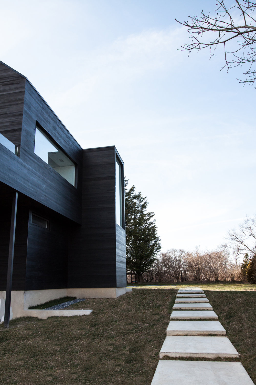 Black Modern barn house with   Shou Sugi Ban cedar siding, windows, and landscaping