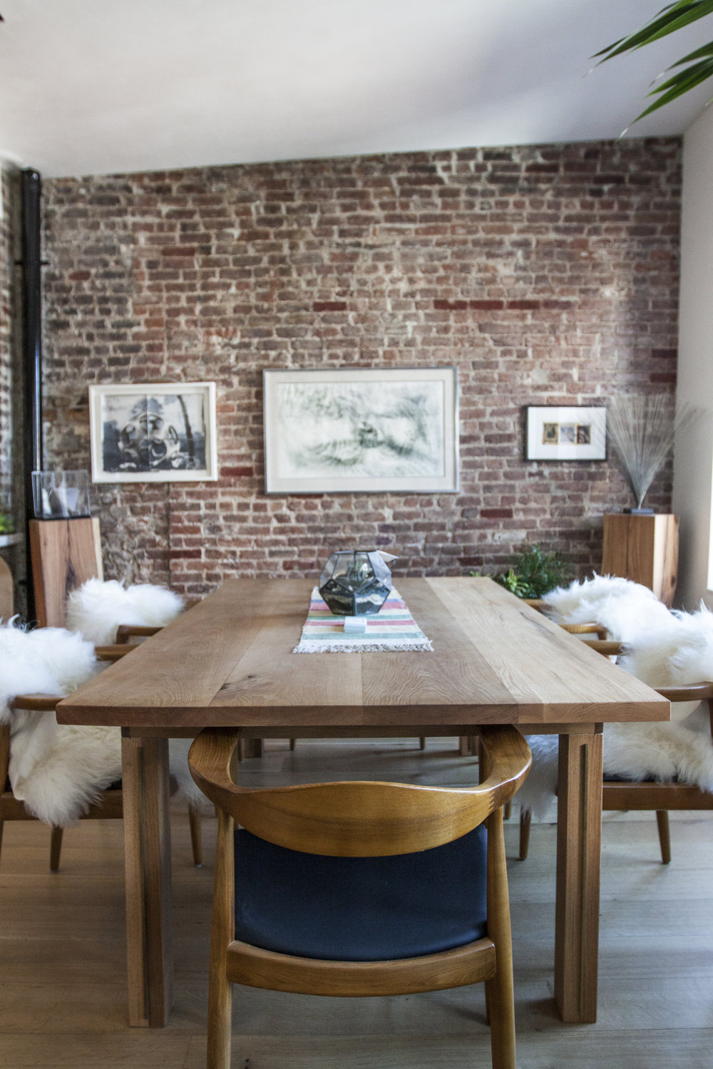 Minimal ZUNG wood oak table with chairs in New York apartment with exposed brick wall