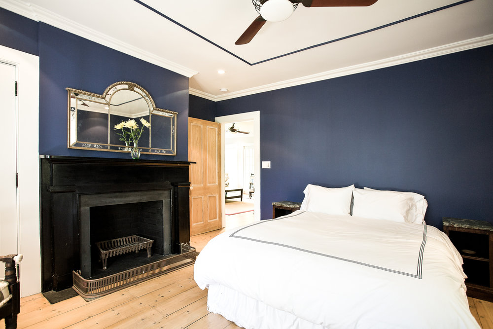 Southampton bedroom minimal royal blue wall black fireplace interior with white bedding