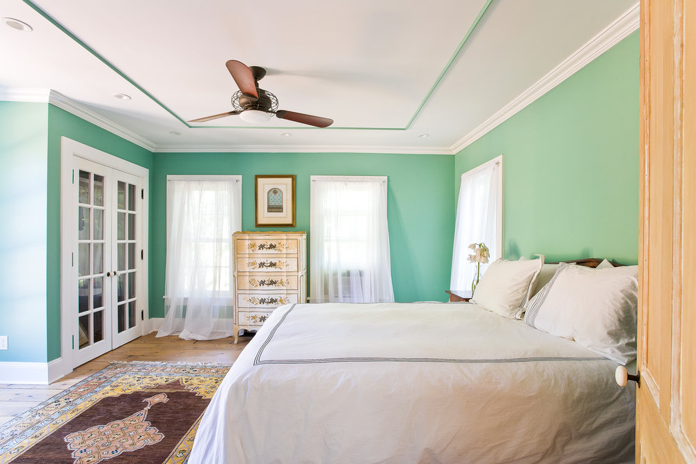 Southampton interior bedroom with green walls, antique furniture and oriental rugs