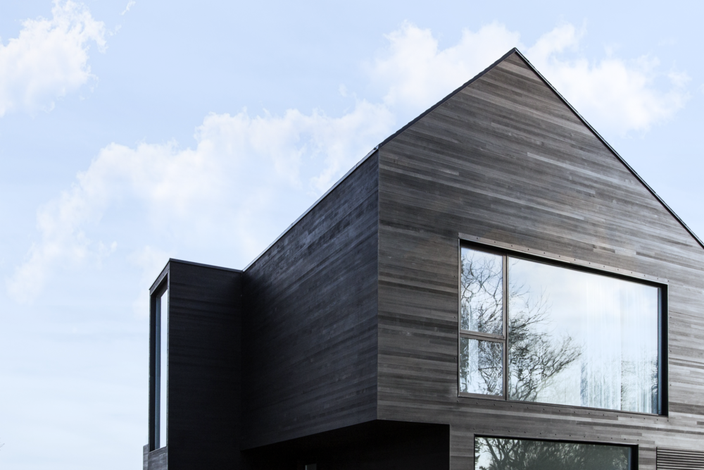 Black Modern A-frame barn house with   Shou Sugi Ban cedar siding and window