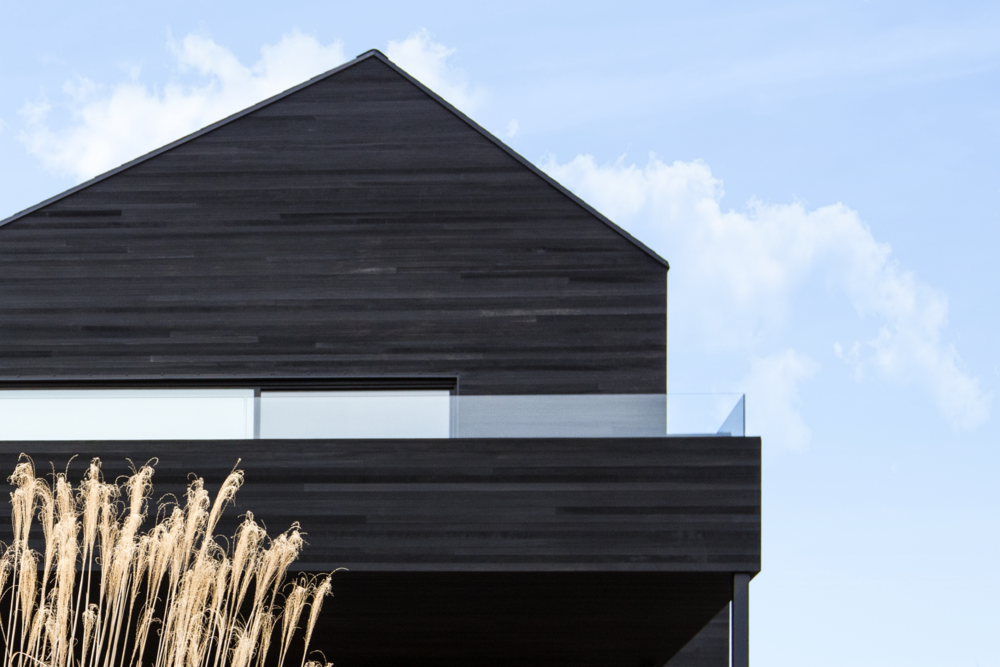 Black Modern barn house with Shou Sugi Ban cedar siding and balcony