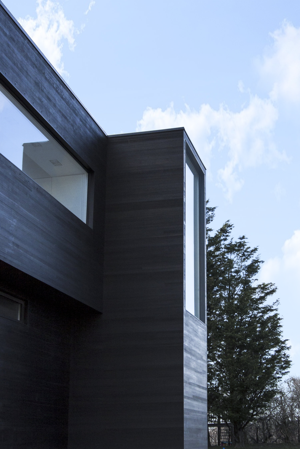 Black Modern barn house with   Shou Sugi Ban cedar siding and window