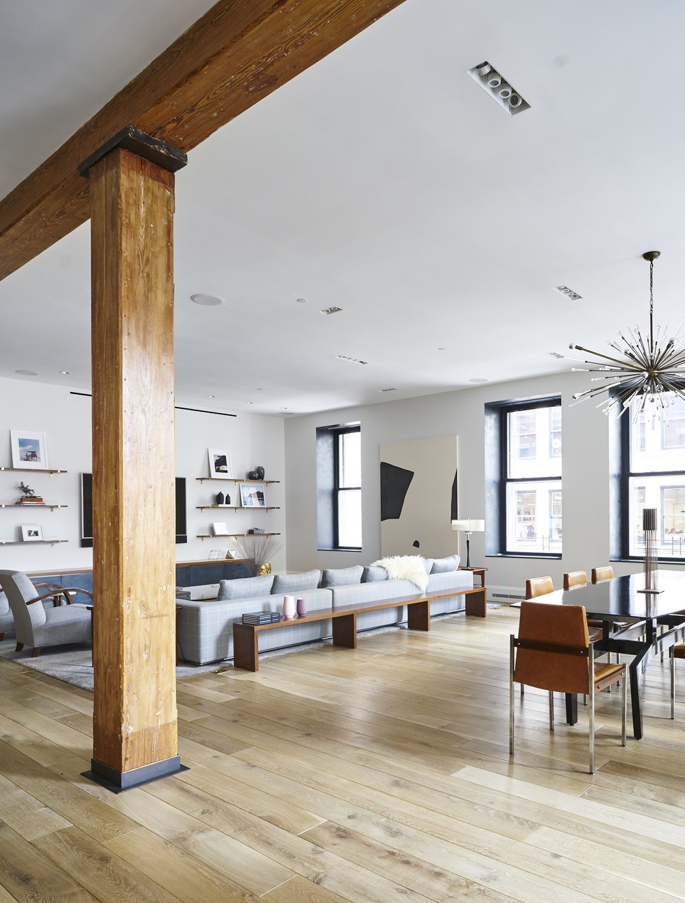 Modern Soho loft renovation living room and dining room with exposed wood beams