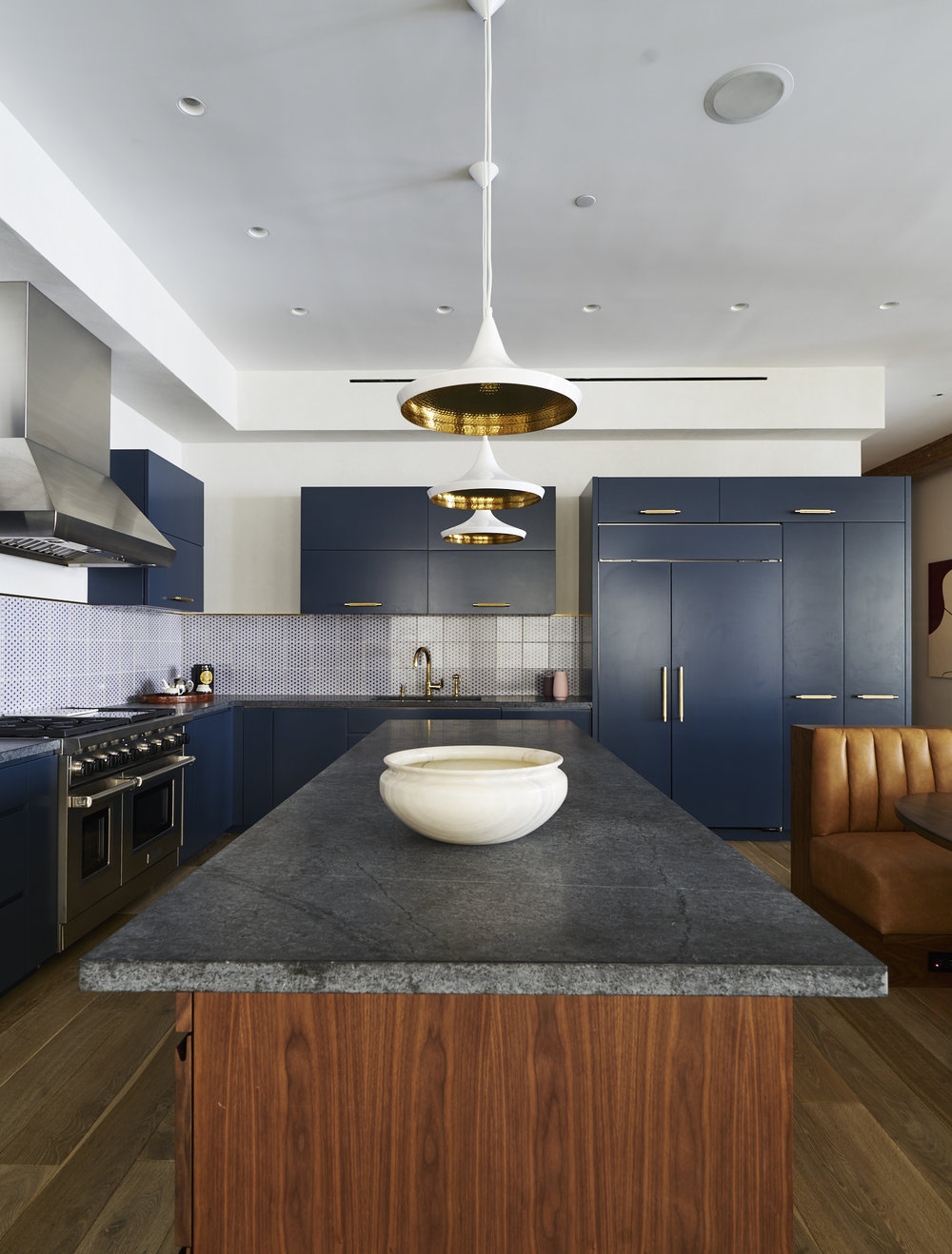 Modern Soho loft renovation blue kitchen with wooden island and brass fixtures