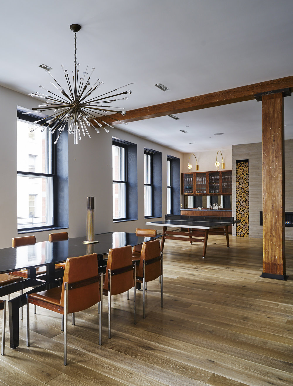 Modern Soho loft renovation dining room with ping pong table, fireplace and open bar