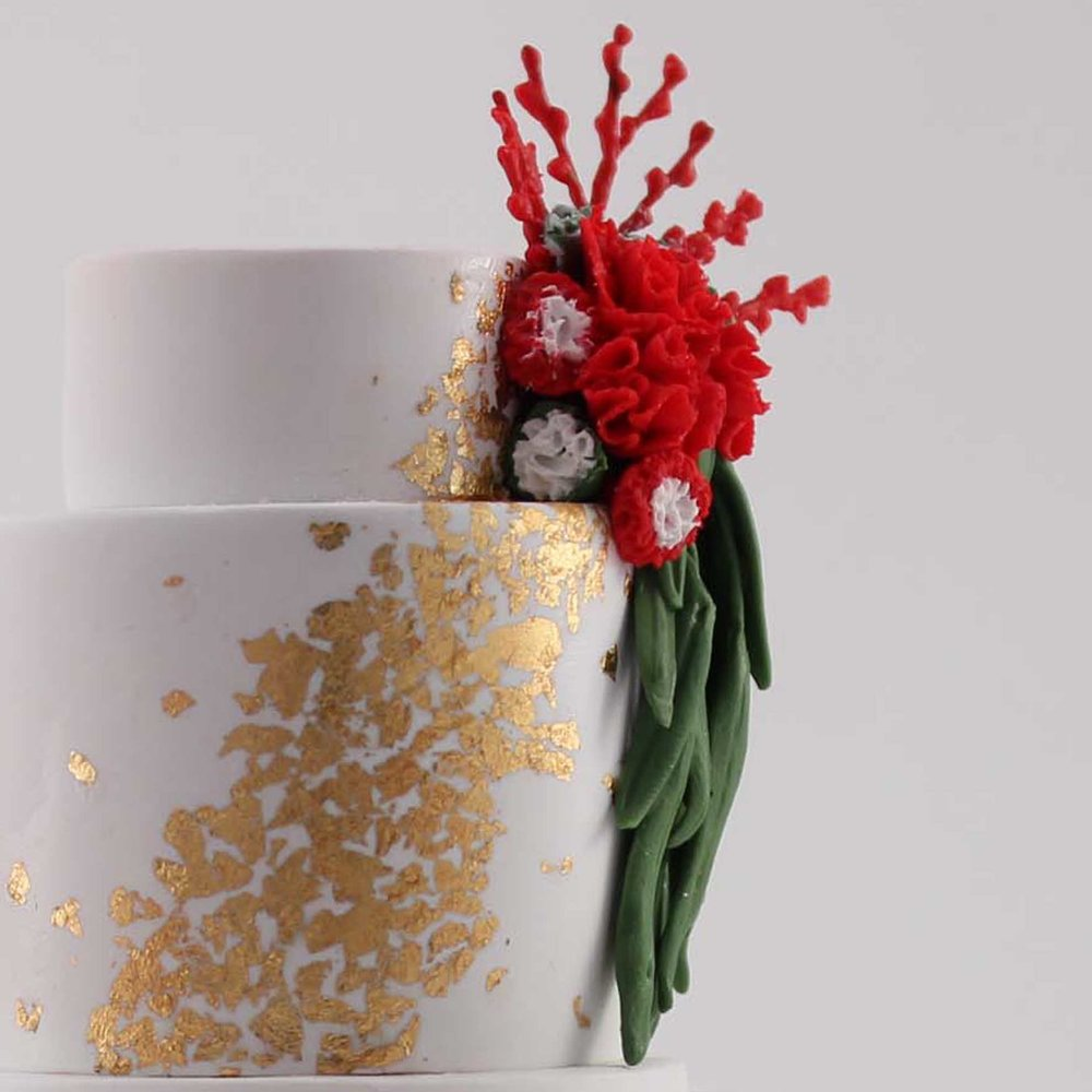 minature replica of gold leaf and red flowers wedding cake detail.jpg