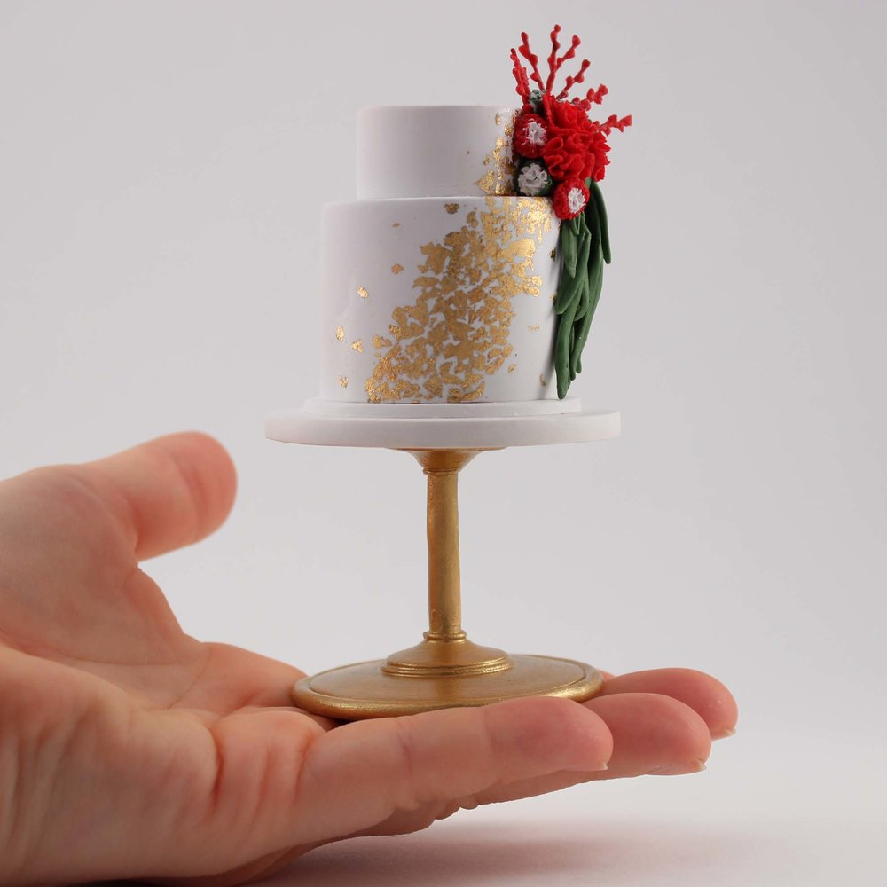 minature replica of gold leaf and red flowers wedding cake.jpg