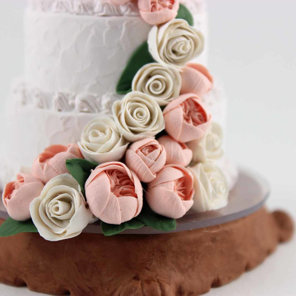 detail of mini wedding cake replica on wooden base.jpg