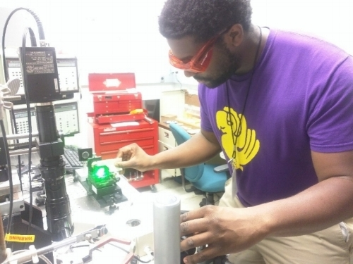 Graduate student summer intern A'Lester Allen, working in Dr. Bin Chen's lab at NASA Ames, is aligning a 532 nm green laser through a photonic crystal (PCF) fiber for measurement of peptides and proteins.