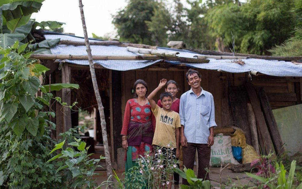 One of our employees standing outside of his temporary home with his beautiful family.