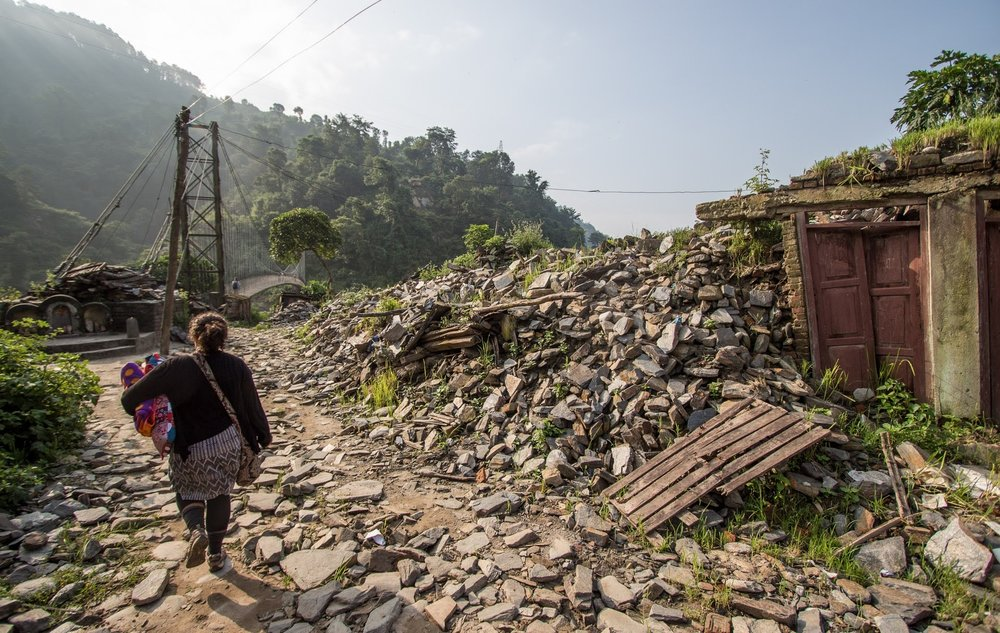 A volunteer walking past rubble of what was once a nearby shop.