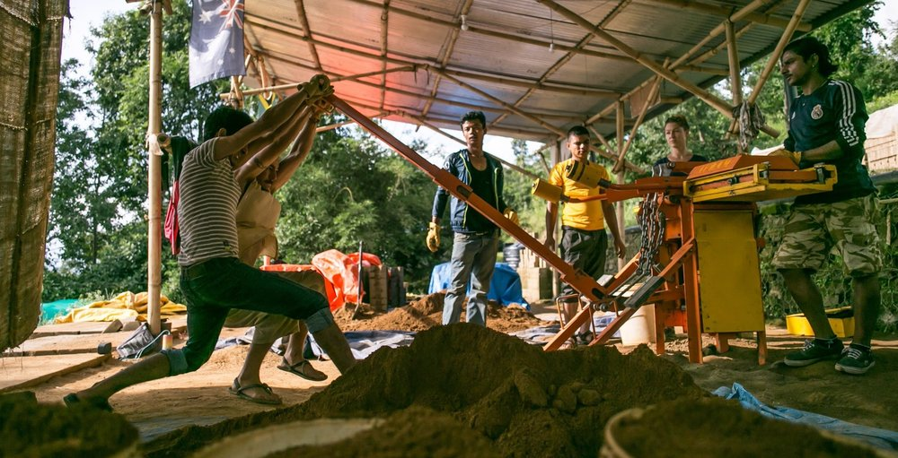 Our Nepali team working with volunteers to produce bricks.