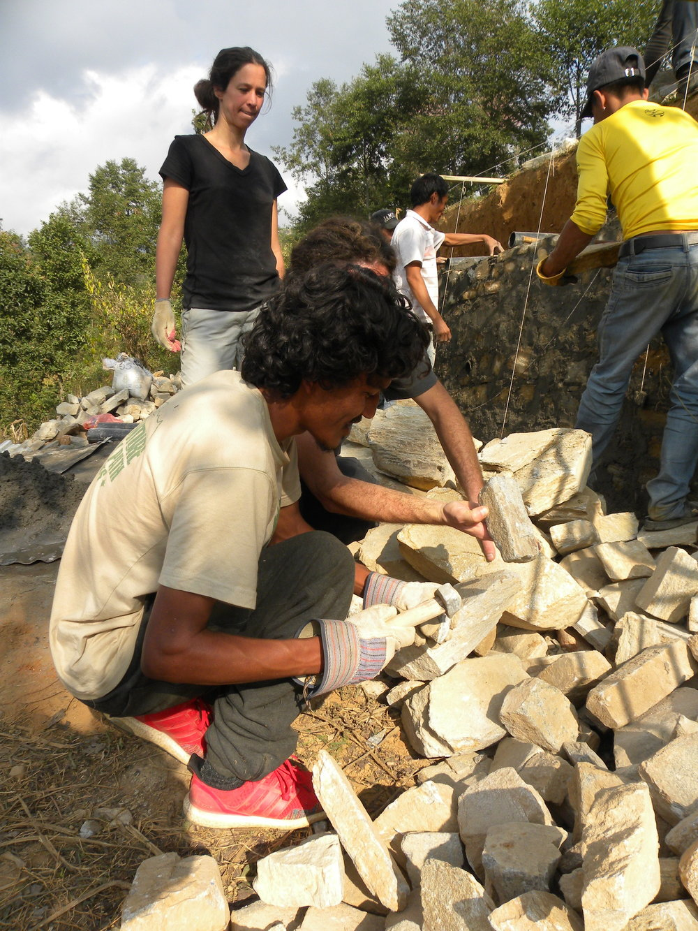 CI Volunteer Joshua helps Maya and Nitzan (behind) move rocks for the gabions.