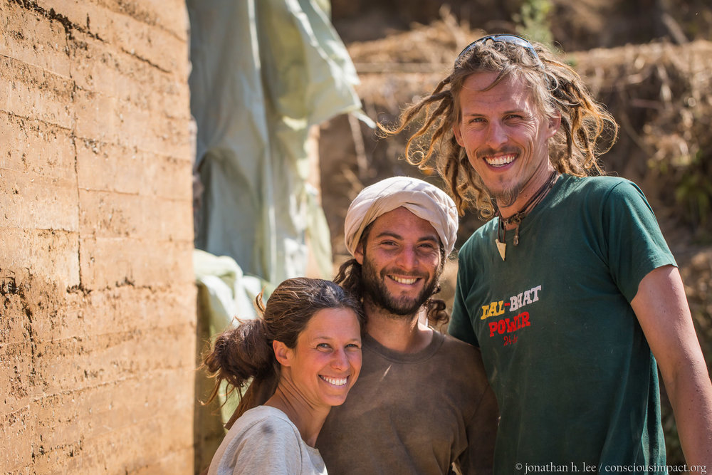 Maya, Nitzan, and Allen pose next to the completed rammed earth walls.