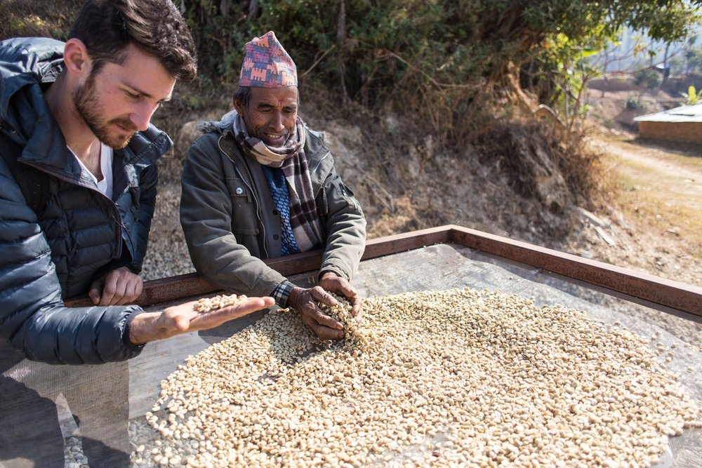 Shyam sharing the coffee production process with John.