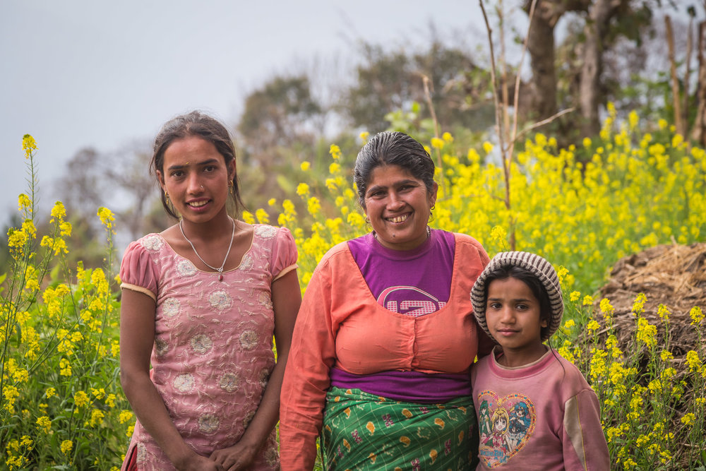 Durga stands in her field with two of her young daughters.