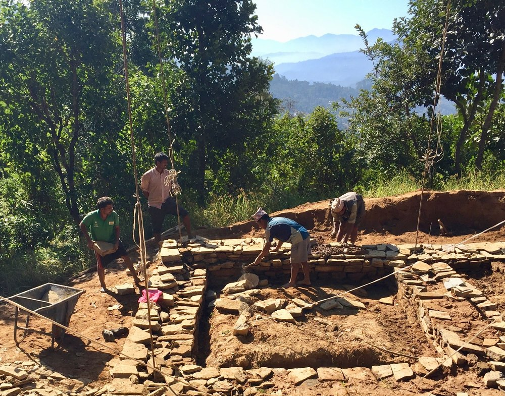 Photo 1: Krishna Kafle, our closest neighbor in Takure, nears the finish of his home's foundation. Now he must decide which bricks to use to complete his walls and strive to finish his home before June. With support, he will rebuild his home with our CSEBs.