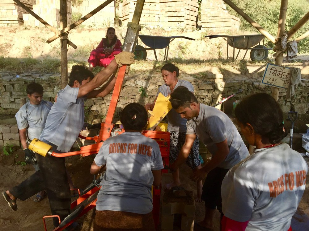 "Photo 3: The Conscious Impact ""Bricks for Nepal"" construction team produces environmentally sustainable and earthquake-safe CSEBs as quickly as possible to be distributed across Sindhupalchok"