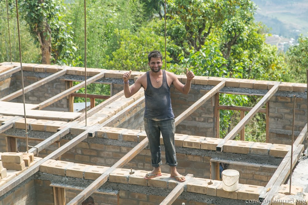 Photo 4: Uddhav Kafle, after two years of working with Conscious Impact, stands on top of his nearly completed home, built with the CSEBs that he helped produce. With the money from his salary, he was able to complete a beautiful, earthquake-safe and environmentally sustainable home for his family that will last for generations to come.