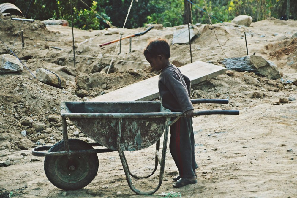 Photo 8: Everyone gets involved in the construction process! A young boy plays with an empty wheelbarrow on site of a local community home reconstruction.