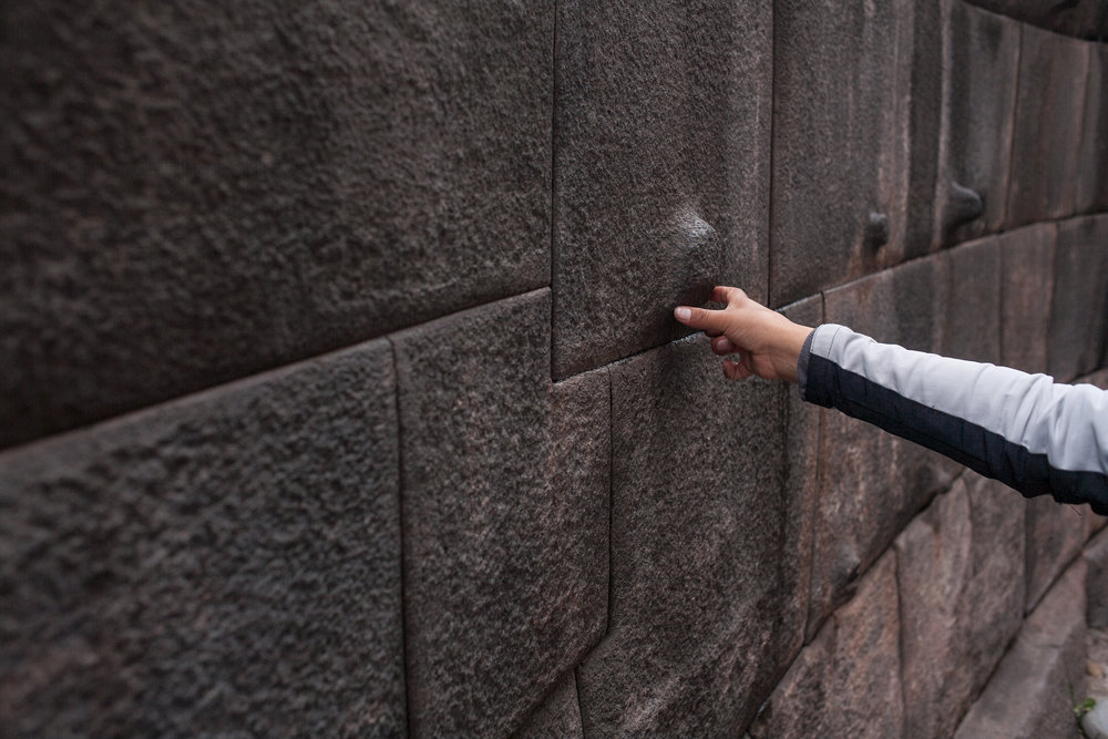 Last week, our Co-Director- Julia Elizabeth Evans - was out of the office.  Her thoughts now concern travel photography.  Taken in Cuzco, Peru - December 2012, a young boy reaches out to touch and then to quickly glide past the incomparable stone walls of ancient Incan architecture.
