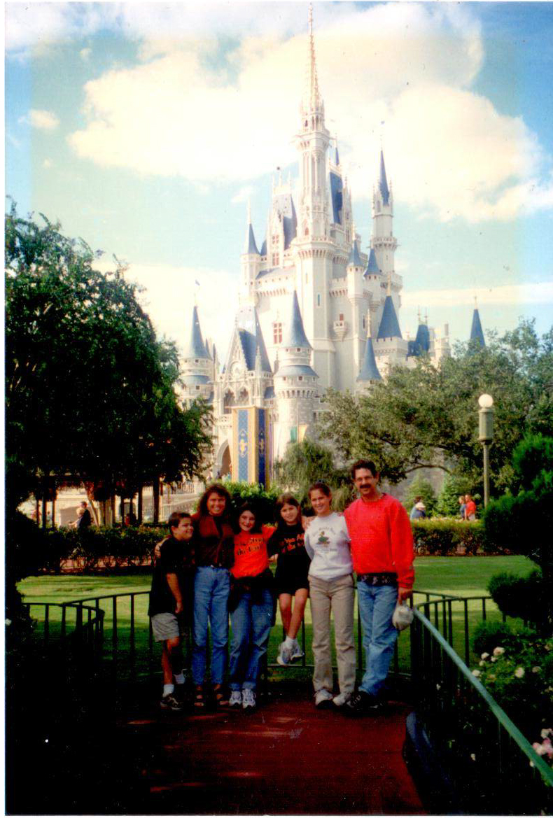 "In the family photo, I'm in the middle, 3rd to the left of the black mustache.  ""Disney World,"" has a 70% return rate.  My family returns every year.  - Julia Elizabeth Evans"