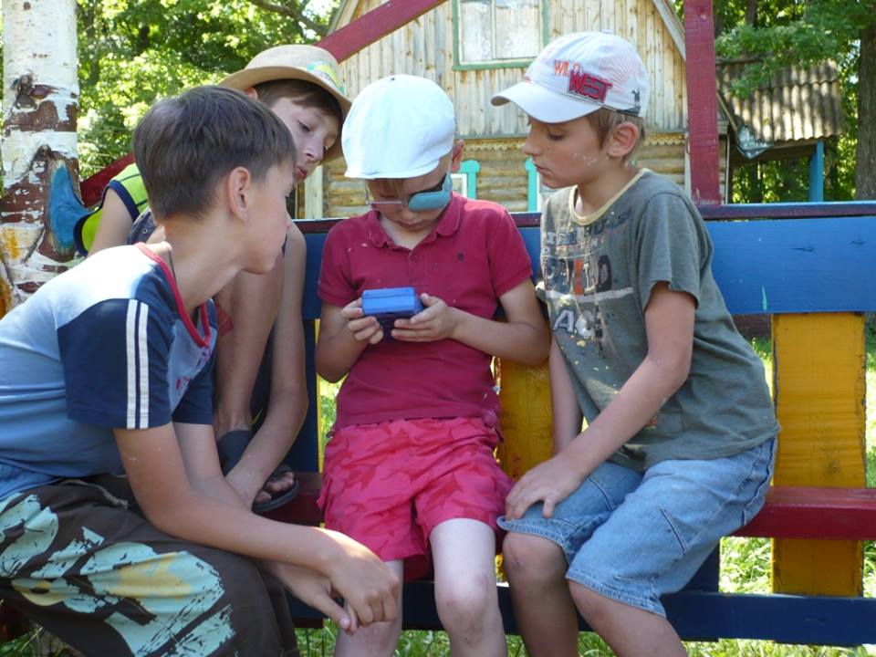 Boys learning to read a radiation dosimeter at one of Viola's bio-intensive and permaculture gardening camps.