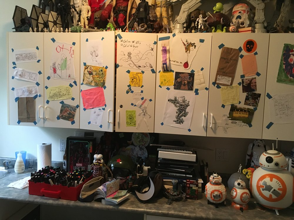 Speaking of keeping yourself inspired, and maintaining some perspective on what you'd like to art up, have a sketch wall if you can. i toss anything I or my offspring have doodled up on these cupboards to keep myself thinking. There's at least four major drawing concepts up there I'm still thinking about what to do with. Also a mismatch of artifacts that make me smile and / or feel inspired. Note that I use a lot of painters tape, stuff that won't hurt the art, and won't strip the walls when you take it down. Also just like the aesthetic of the blocky, easy tear tape.