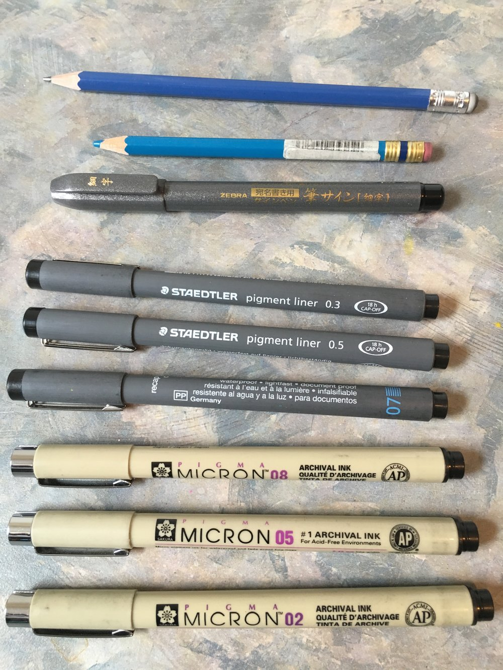 For my line art, these are my standards. More delicate artists will use finer calibers of pen, like 0.01 and 0.05 to get those engineering blueprint fine kinds of detail, however I find I end up destroying the nibs on pens that skinny at a costly rate, so I tend to stick with bigger, heartier fare.   I prefer Staedtler for general, HB (dead even between light and dark) pencil, though lately I've shifted away from graphite to using animation pencils for my initial sketching. I swear by the Col-Erase brand, esp. blue red, and purple, and I must not be alone as the one's I like are typically the low or no stock at the local art shops.   I use Staedtler Pigment liners when I'm being more sketchy and playful when I ink, likely due to a less defined initial sketch. For more deliberate, delicate, or precision inking, I prefer the Pigma Microns, the have less flexibility in their tip, but deliver a smooth, consistent, beautiful black like that leaves little room for surprise that this is the pen European and Japanese artists default to for fine line inking.