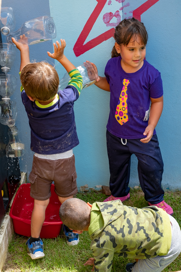 Pre-schoolers play at the makeshift waterfall