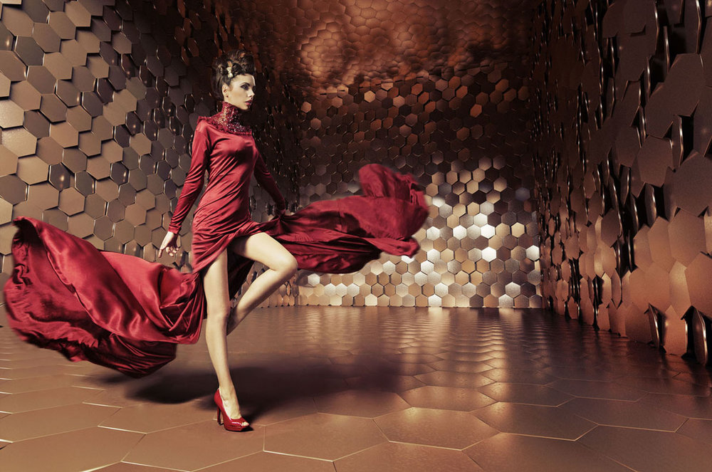 A lady dancing in a red dress inside a box filled with bronze and gold hexagons