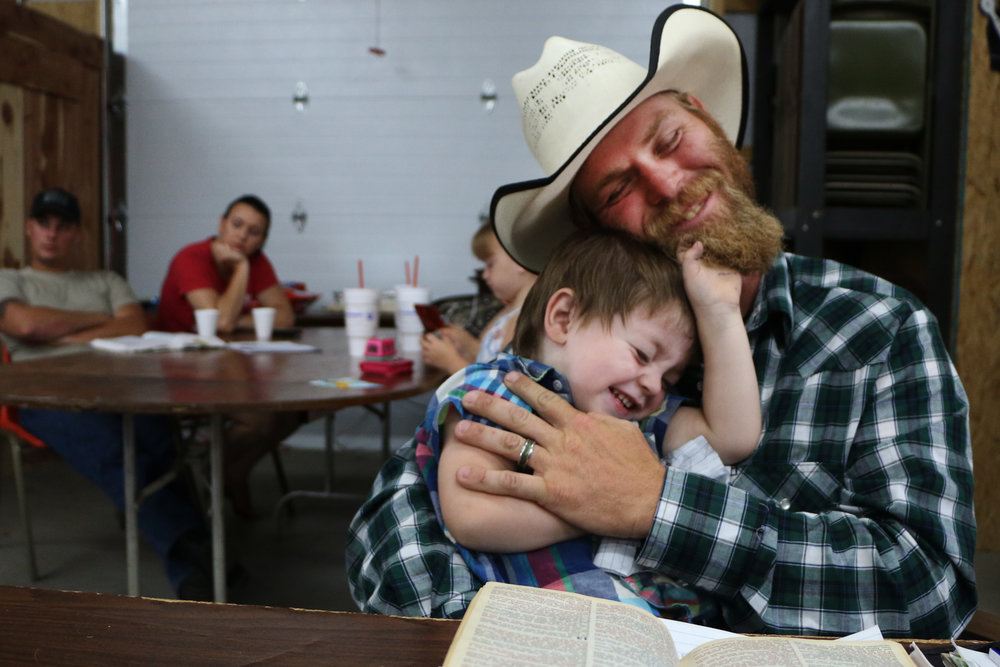 Hank Parker, of McFarland, plays with his son Colton, 2, during a sermon.
