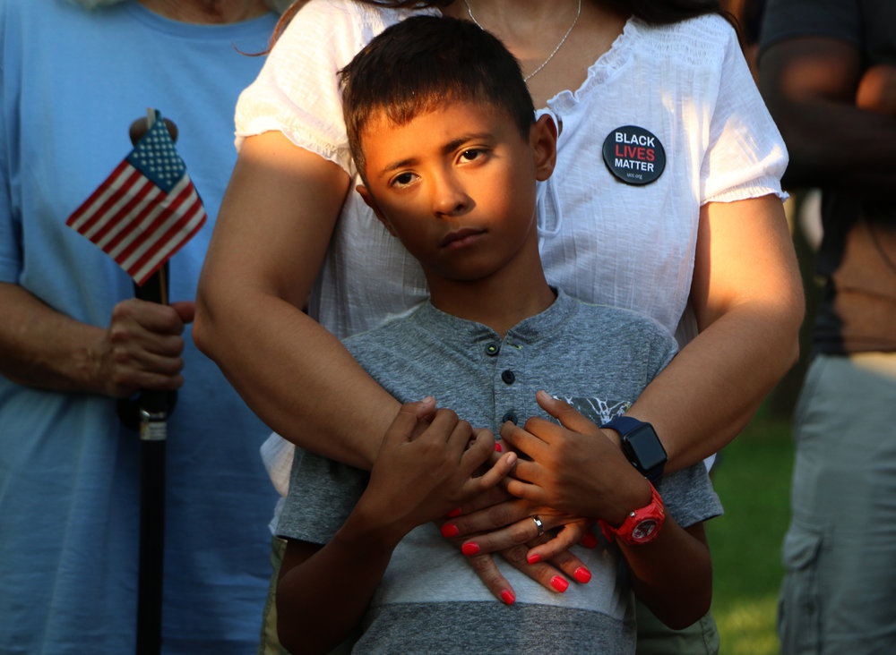 Alex Markson, 9, of Manhattan, is held by Heather Morse at a vigil for those who died in Charlottesville hosted by the Manhattan Alliance for Peace and Justice on August 13, 2017.
