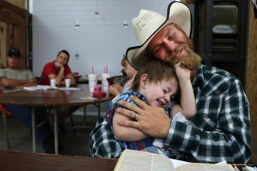 Hank Parker, of McFarland, plays with his son Colton, 2, during a sermon at the Cowboy Country Church in Wamego on July 16, 2017.