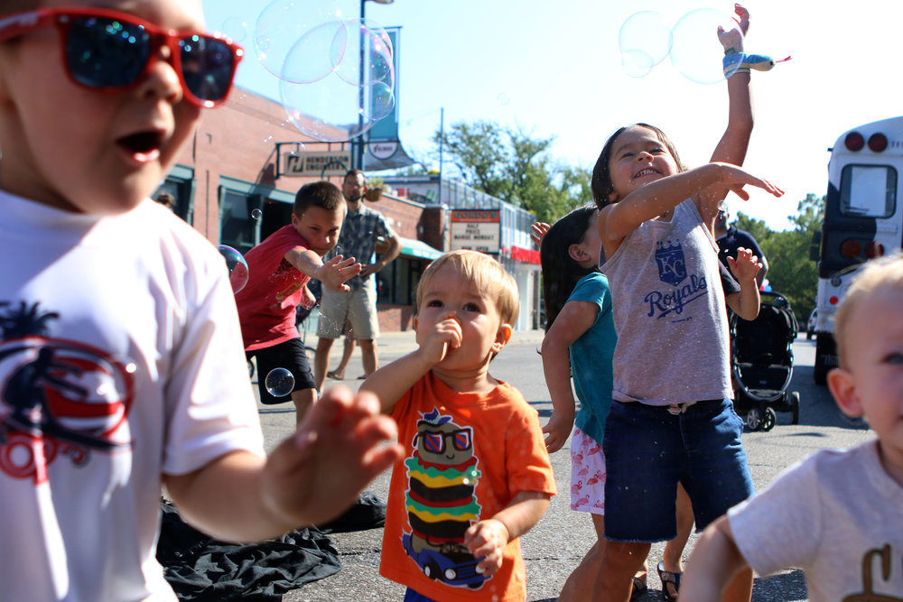 Kids chase bubbles at the Mini Maker Faire in Aggieville on Sept. 23, 2017.