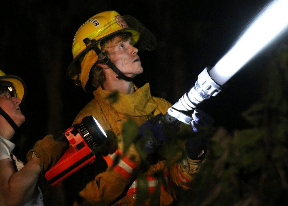 Timothy Gunter, a firefighter for Station 12, puts out his first structure fire as Dorothea Palmer holds a light on Sept. 9, 2017.