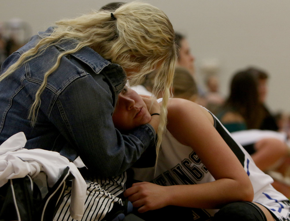 Demi Kunkel, a Rock Creek senior, comforts Lany Scott during Tuesday's game. Kunkel was injured in a previous game and could no longer play.