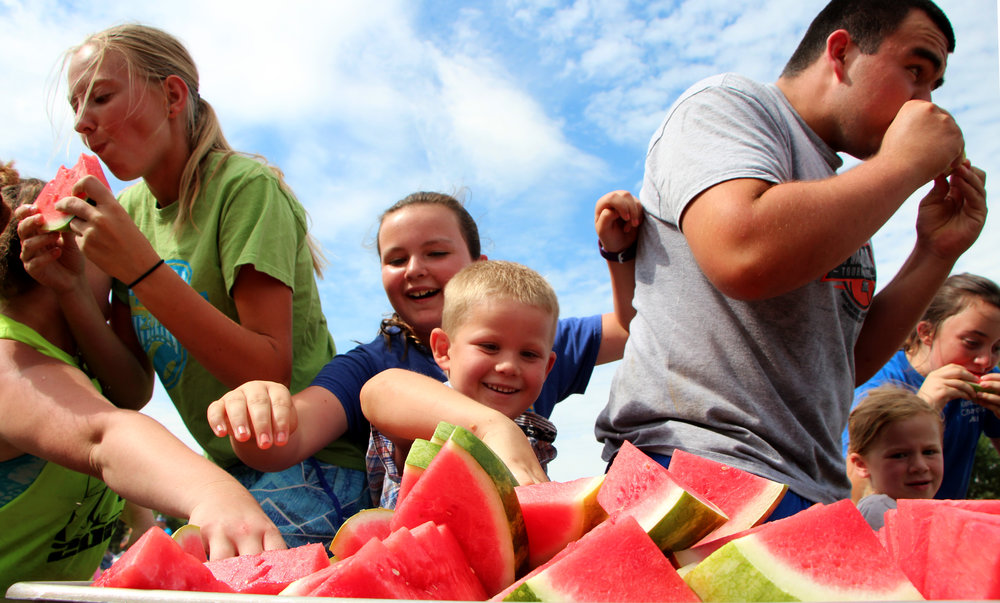 Participants race to eat watermelon during a race at the Fair Olympics in Cico Park in Manattan, KS on July 30, 2018.