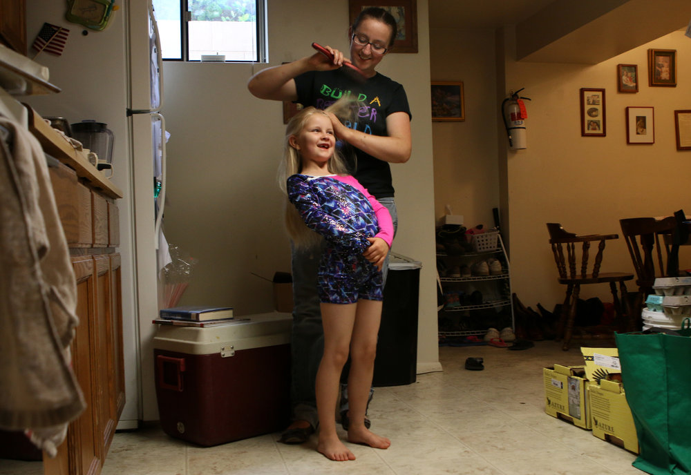 Allison Booth brushes on Azeyl Booth's hair in their kitchen Azeyl went to dance practice on Ocotber 12, 2017.