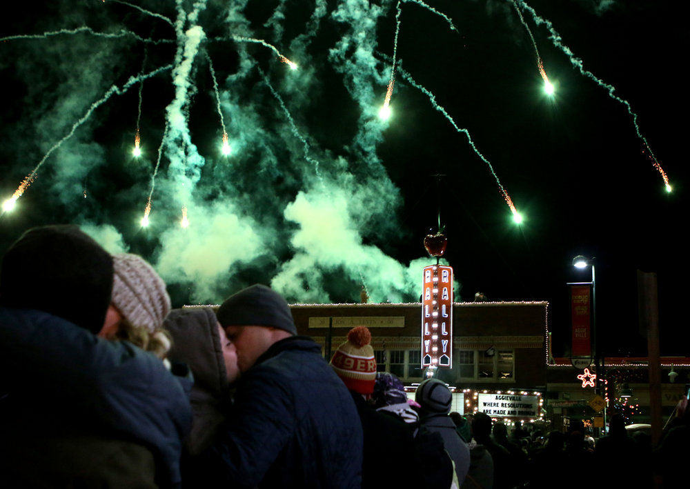Regan and Charlotte Lundin, second from left, share a kiss at the stroke of midnight on Jan. 1, 2018 during a New Year's Eve Celebration in the Aggieville neighborhood of Manhattan, Kansas.